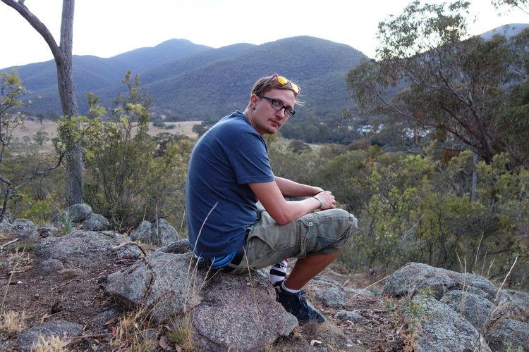 Portrait of man sitting on rock