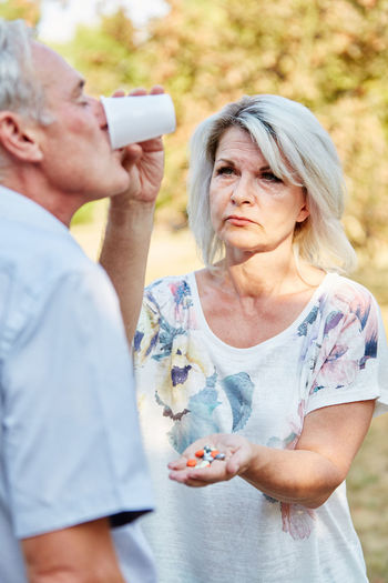 Mature woman giving medicines to senior man in park