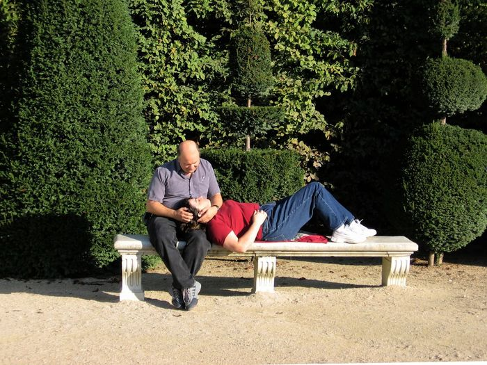 A very normal couple, just relaxing on a bench and looking at each other with a romantic look. Romantic Adult Adults Only Casual Clothing Couple In Love Day Full Length Leisure Activity Men Nature One Couple One Person Only Men Outdoors People Plant Real People Relaxation Romantic Look Sitting Tree