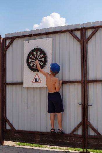 Rear view of boy holding dartboard on wall
