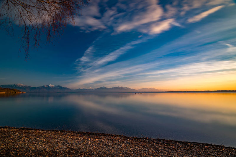 Scenic view of chiemsee lake against sky during sunset