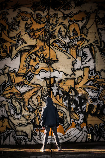 Rear view of man standing against graffiti wall