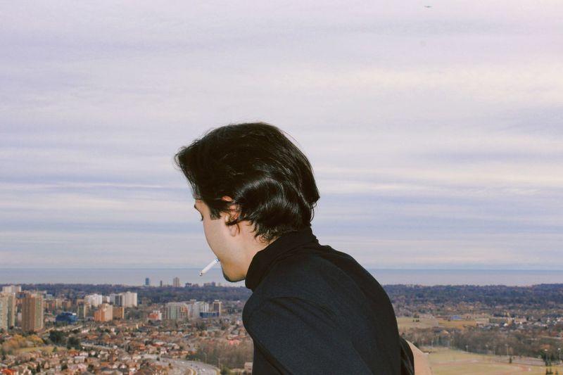 Man smoking cigarette against cityscape