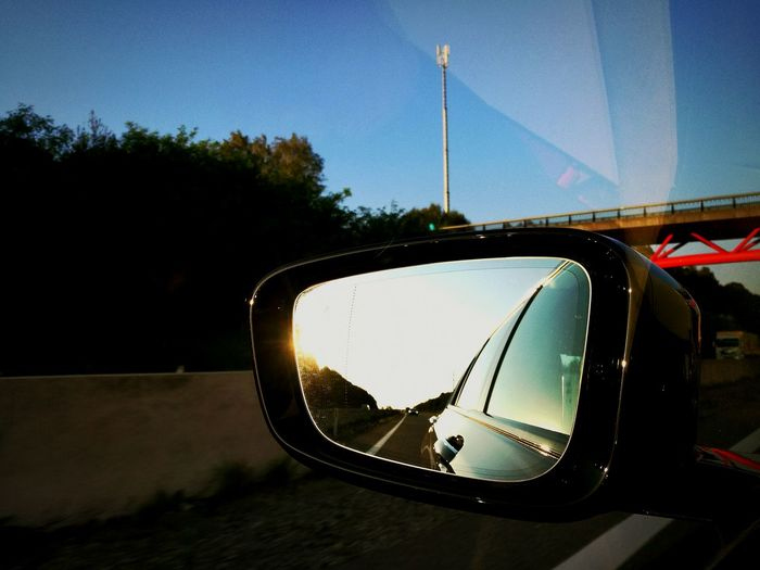 Behind the way Side-view Mirror Transportation Car Reflection Land Vehicle Mode Of Transport Road Tree Street Road Trip Clear Sky Close-up Focus On Foreground Vehicle Day Outdoors Sky Blue No People