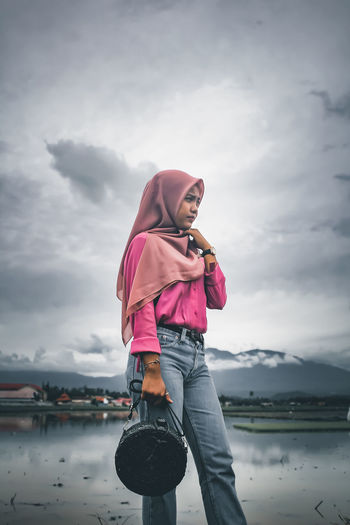 Teenage girl with bag wearing hijab standing by lake against sky
