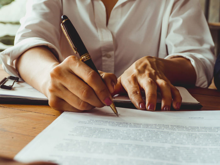 Signing a business contract for the goal of success. Concepts for the future of the business that will improve Human Hand Hand Table Real People Paper Pen Indoors  Writing One Person Holding Human Body Part Men Midsection Desk Furniture Document Communication Sitting Occupation Studying