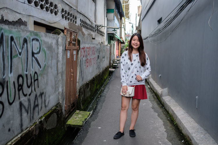 Portrait of smiling young woman standing amidst wall in city