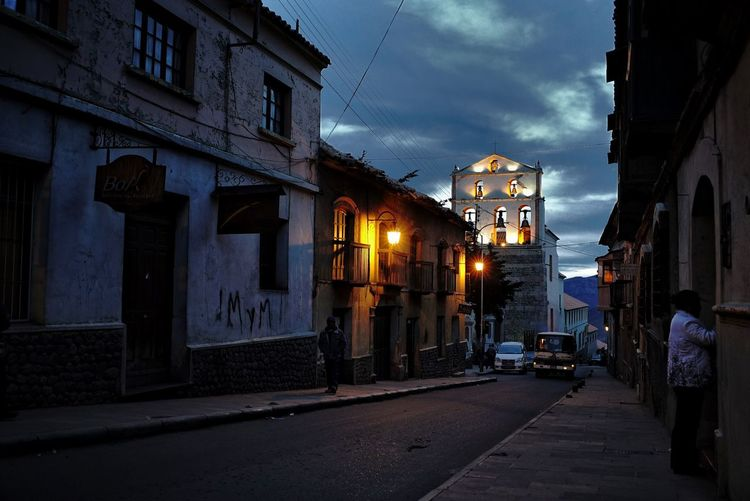Illuminated city street against sky at night