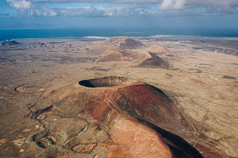 Calderon Hondo Volcano Mountain Landscape Rock Volcano Tourism Nature View Sky Crater Summer Island Travel Scenics Volcanic Landscape Europe Geology Natural Corralejo Area Energy Thermal Aerial View View From Above Ground Outdoors Heat Park Birds Eye View Drone  Landmark Aerial Backgrounds Geothermal  SPAIN Calderón Calderon Hondo Canary Islands Arid Climate Hiking Fuerteventura Nobody Reserve Panorama Terrain Surface Above