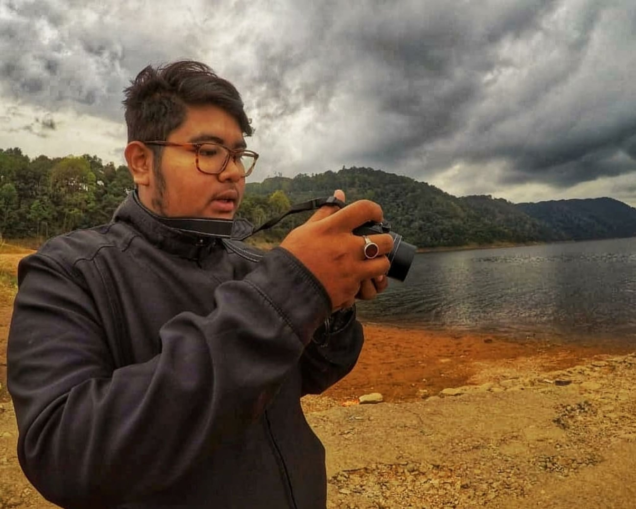 water, waist up, glasses, one person, cloud - sky, sky, men, nature, eyeglasses, standing, adult, males, lake, portrait, looking, mid adult, holding, casual clothing, mature adult, outdoors, mature men, contemplation