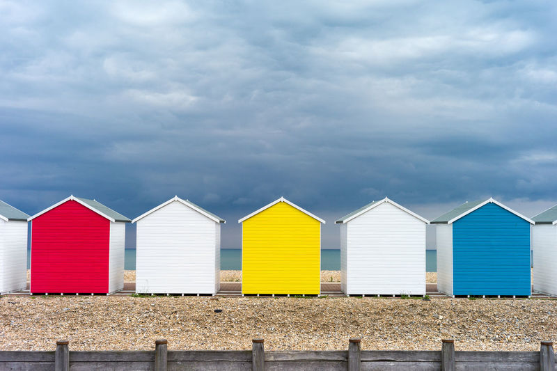 Colorful beach huts against cloudy sky