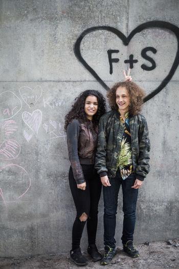 Portrait of happy friends standing against graffiti wall