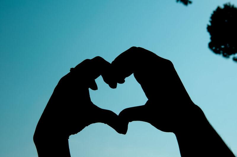 Silhouette man making heart shape against clear blue sky