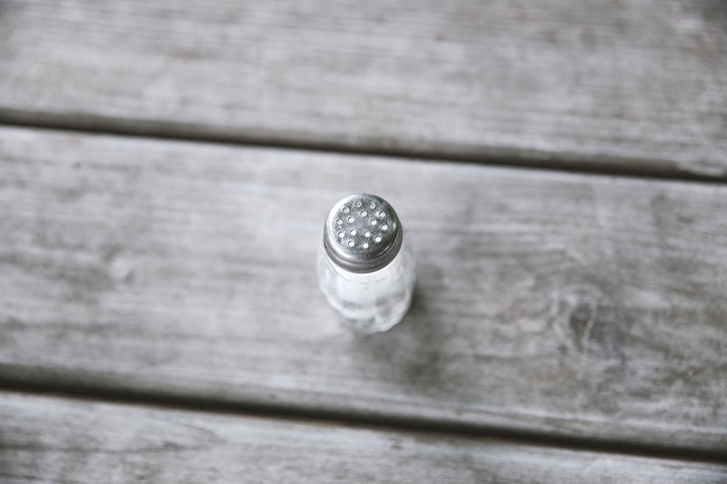 Salt shaker on the table Bistro Cooking Cuisine Household Background Close-up Day Food Glass - Material High Angle View Indoors  Metal No People Restaurant Salt - Mineral Salty Selective Focus Shaker Sodium Spice Steel Table Tasty White Wood - Material