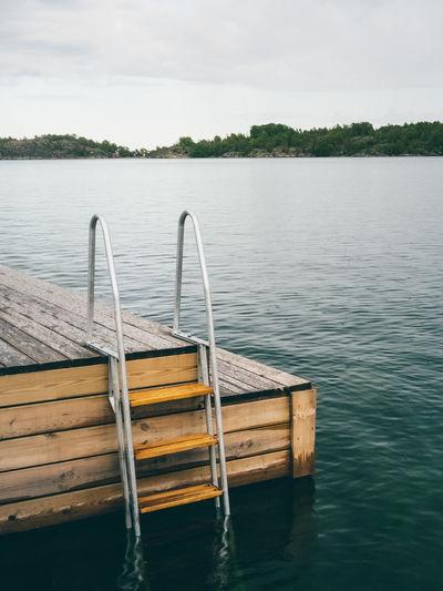 Wooden boat in lake against sky