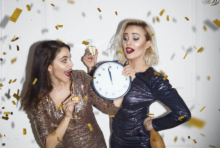 Happy women looking at time while holding drink during party