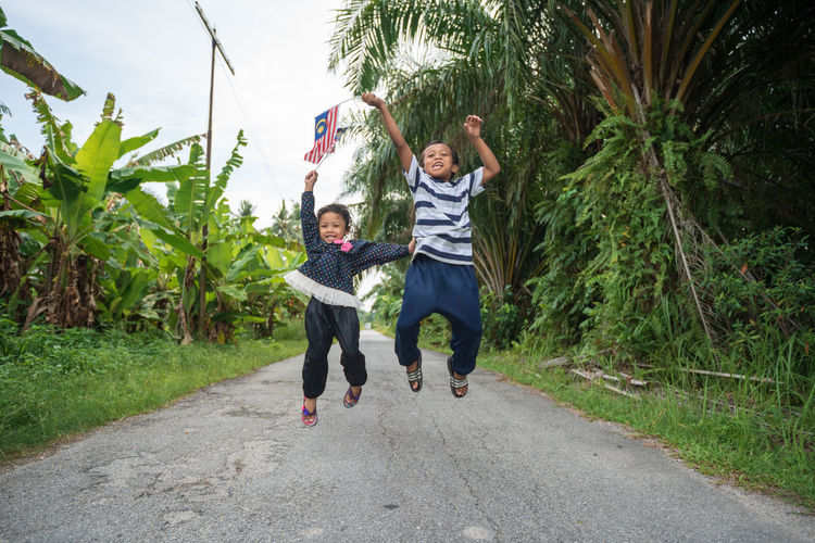 Siblings Holding Malaysian Flag While Jumping On Road Amidst Plants
