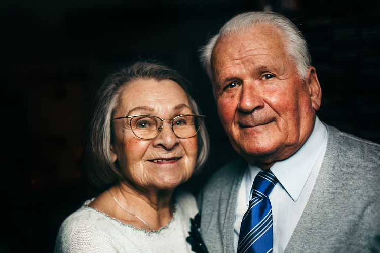 Close-Up Portrait Of Senior Couple Smiling In Darkroom