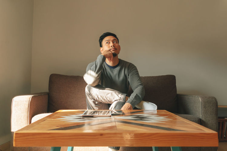 Portrait of man sitting on sofa