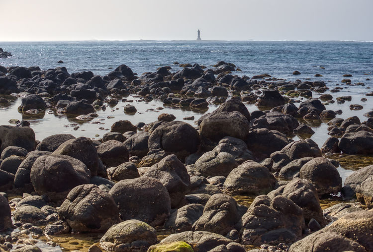 Lighthouse in front of the Almadies Sea Water Rock Solid Beach Land Sky Rock - Object Scenics - Nature Beauty In Nature Nature Horizon Horizon Over Water Tranquil Scene Tranquility Day Stone - Object Stone No People Pebble