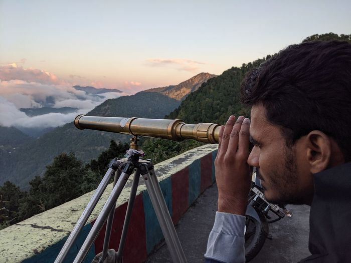 Young man looking at view through telescope