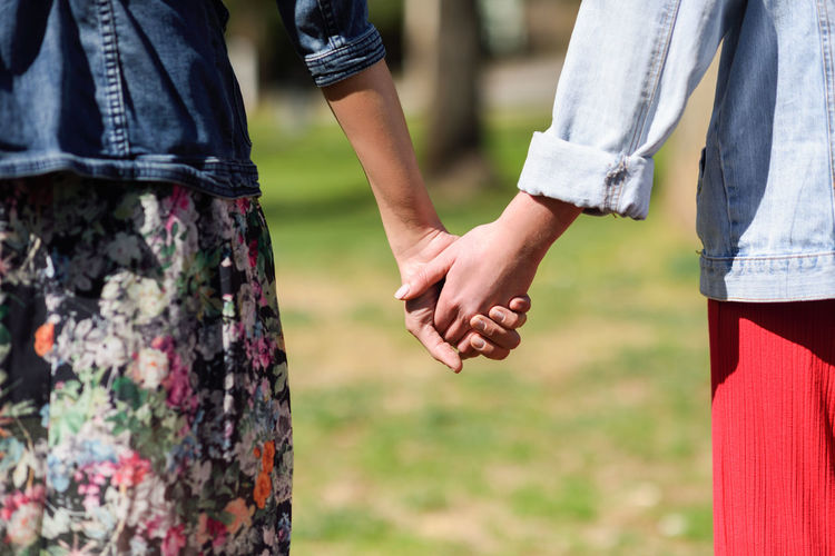 Two young women in walking holding her hands in urban park. Lifestyle concept. Rear view. Adult Bonding Casual Clothing Couple - Relationship Day Emotion Focus On Foreground Hand Holding Hands Human Body Part Human Hand Jeans Love Men Midsection Outdoors People Positive Emotion Real People Togetherness Two People