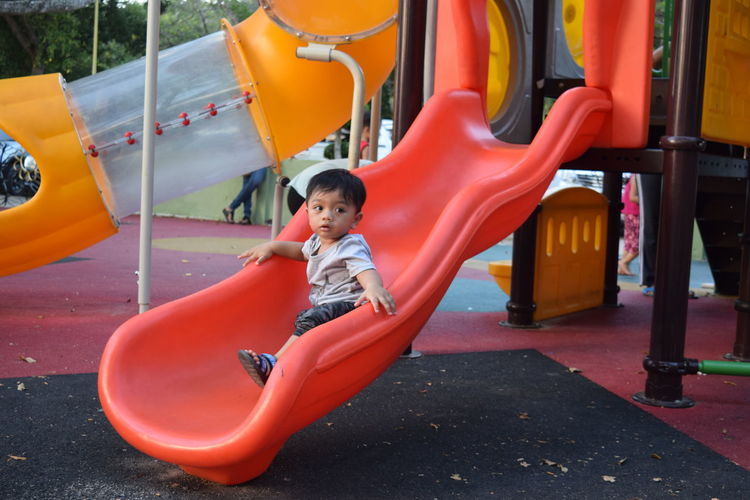 Cute boy looking away while playing in playground