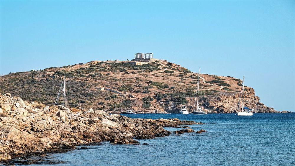 The Temple of Poseidon in Cape Sounio, Attica Greece - Ancient Antiquity Architecture Blue Building Exterior Built Structure Calm Clear Sky Cliff Distant Nature Rock - Object Rocky Scenics Sea Shore Sounio Stone - Object Temple Tranquil Scene Tranquility Water