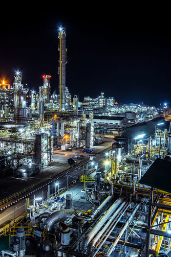 High angle view of illuminated factory against sky at night