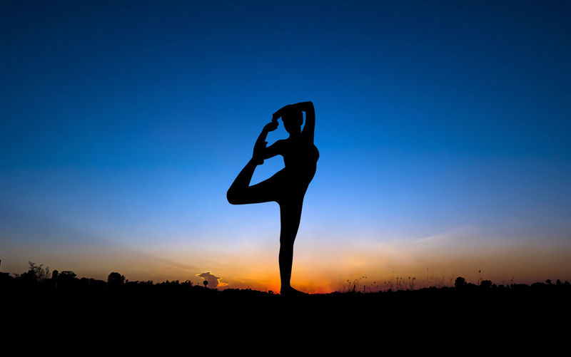 Low angle view of silhouette woman stretching against sky during sunset