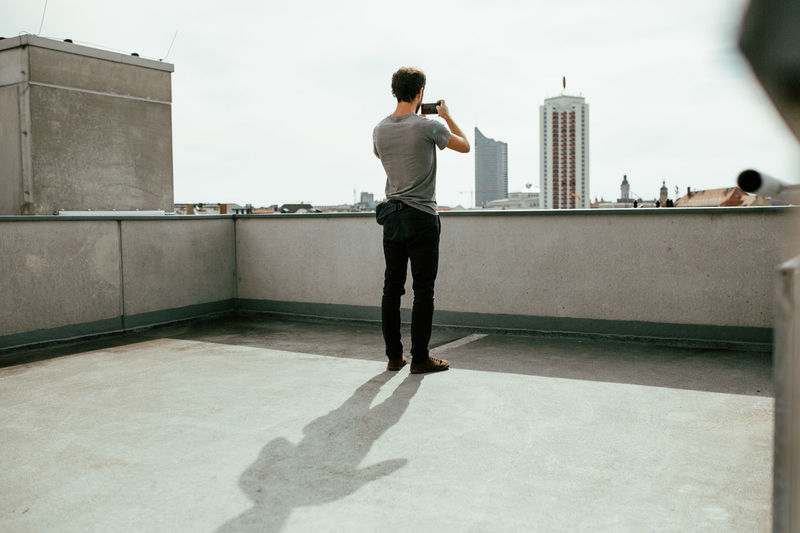 Young man photographing a city skyline with his smartphone Built Structure One Person Architecture Building Exterior Full Length Rear View City Standing Real People Building Wall Leisure Activity Men Outdoors Day Casual Clothing Terrace Cityscape Summer Summertime Travel Destinations Photography Photographing Technology Smartphone