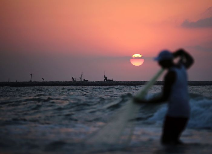 Man holding fishing net while standing in sea against sky during sunset