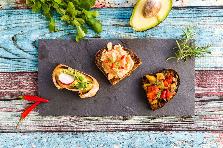 Three different kind of Bruschetta (roasted Bead) on a black plate against colourful wooden table. Food Food And Drink Freshness Healthy Eating Wood - Material Vegetable Bread No People Herb Garnish Snack SLICE Bruschetta Roasted Bread Vegan Vegetarian Food Summer Vegan Food Avocado Wellbeing Ready-to-eat Indoors  Yummy Freash Bell Pepper Tasty Tasty Dishes BBQ