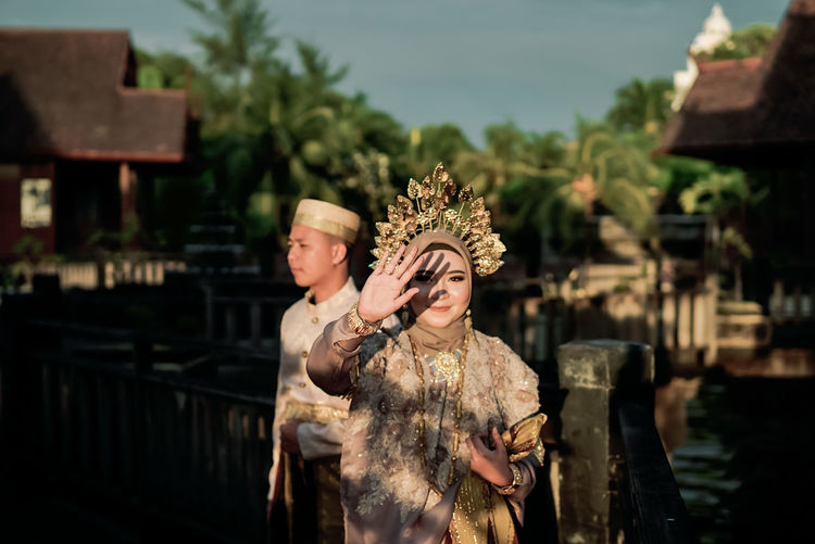 Portrait of bride wearing traditional clothing shielding eyes while standing with groom