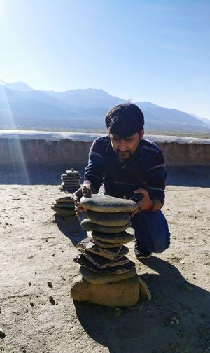 Full length of man stacking stone outdoors