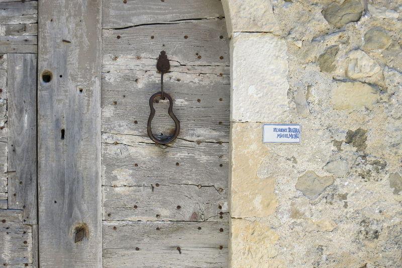 Close-up of hook hanging on wooden door