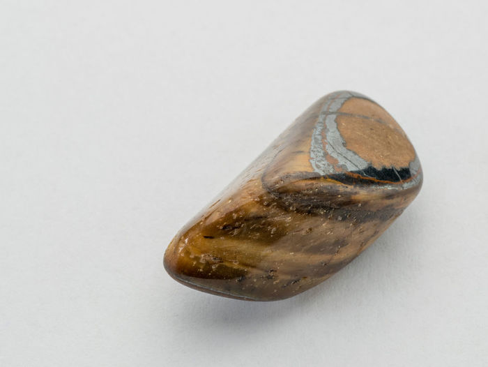 Tigers eye gemstone. Beautiful natural crystal gemstone. Macro shot. Tigers Eye Gemstone Close-up Gemstone Jewelry Gemstones Single Object Studio Shot White Background