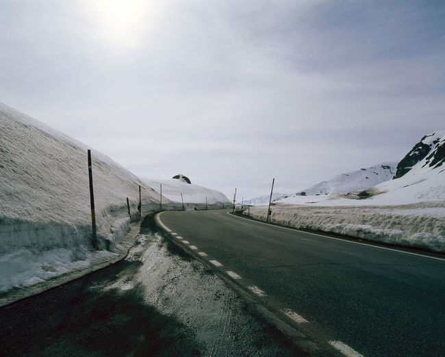 An empty asphalt road in the snow covered landscape in alps switzerland Asphalt Holiday Snow ❄ Travel Winter Beauty In Nature Cold Temperature Day Landscape Mountain Nature No People Outdoors Road Road Trip Scenics Sky Snow The Way Forward Transportation Vacation Winter