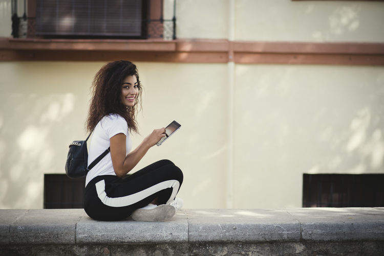 beautiful young woman with backpack using her tablet in the street Adult Architecture Beautiful Woman Beauty Communication Full Length Hair Hairstyle Long Hair Looking At Camera One Person Outdoors Portrait Real People Sitting Technology Wall - Building Feature Wireless Technology Women Young Adult Young Women