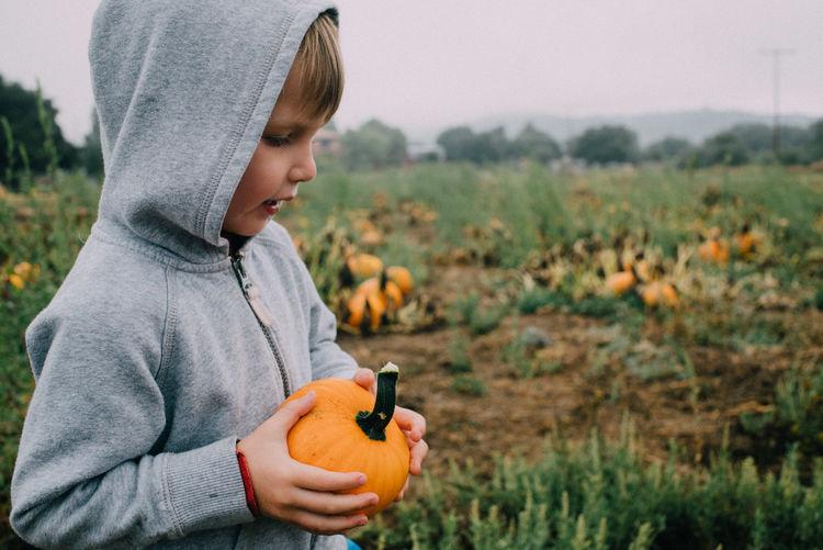Full length of boy holding pumpkin on field