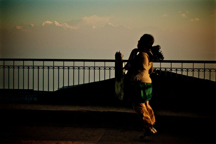 Rear view of woman on bridge against sky during sunset