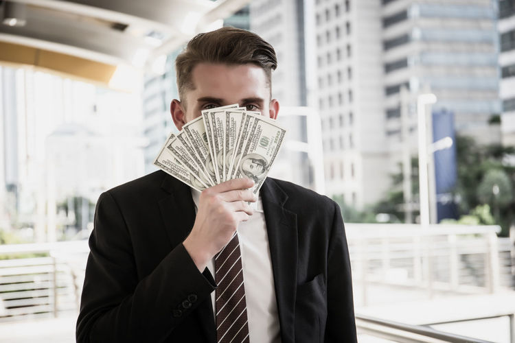 Businessman covering face with paper currency while standing in city