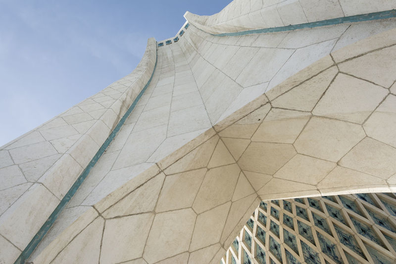 TEHRAN, IRAN - 7 May 2018 low angle viewpoint of Azadi tower formerly known as the shahyad tower in Tehran Low Angle View Built Structure Architecture Sky Building Exterior Day No People Nature Pattern Travel Destinations Sunlight Outdoors White Color Clear Sky Modern Art And Craft Tourism City Travel Historical Building Architectural Detail Azadi Tower In Tehran Mosaic Tiles