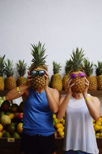 Women Covering Faces By Pineapples