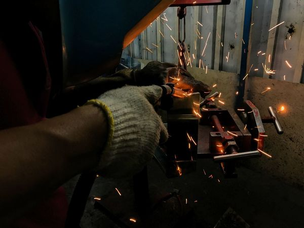 man welds at the factory Sparks and smoke Presenting the concept in the industry. Close-up Day Factory Flame Heat - Temperature Human Hand Illuminated Indoors  Making Metal Industry Occupation One Person People Real People Welds Working Workshop