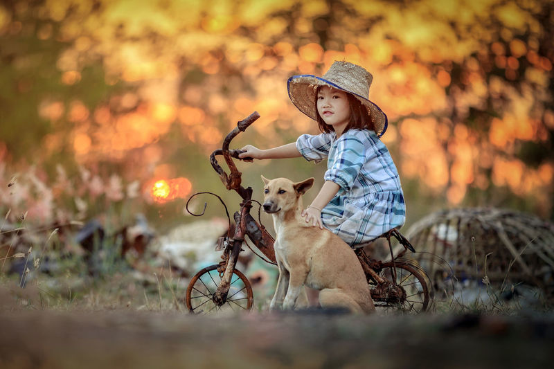 Cute Girl With Dog Riding Bicycle Against Trees