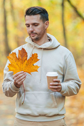 Man holding maple leaf during autumn