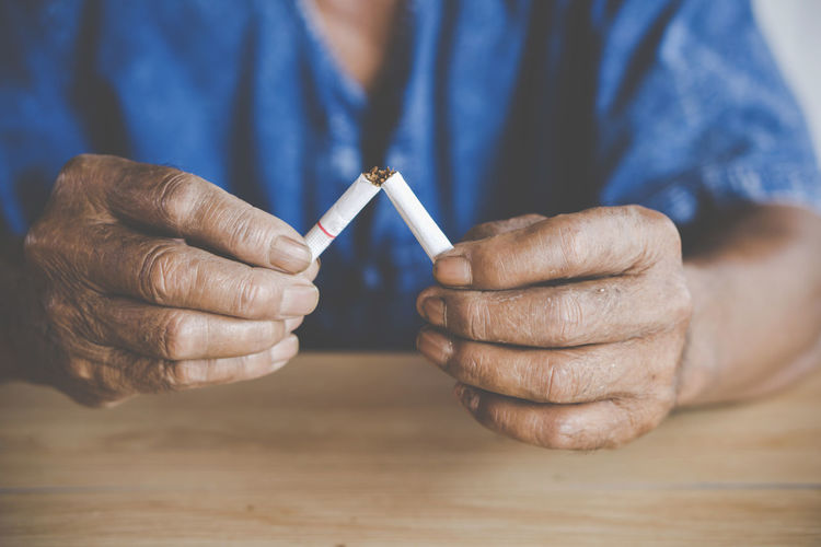 no smoking day concept with old male hand crushing cigarette closeup Cancer Cutting Freedom Healthcare Lifestyle Living Smoking Addiction Cancel Ciggarette Close-up Destroy Finger Hand Holding Illness No Old Smoker Social Issues Stop Unhealthy