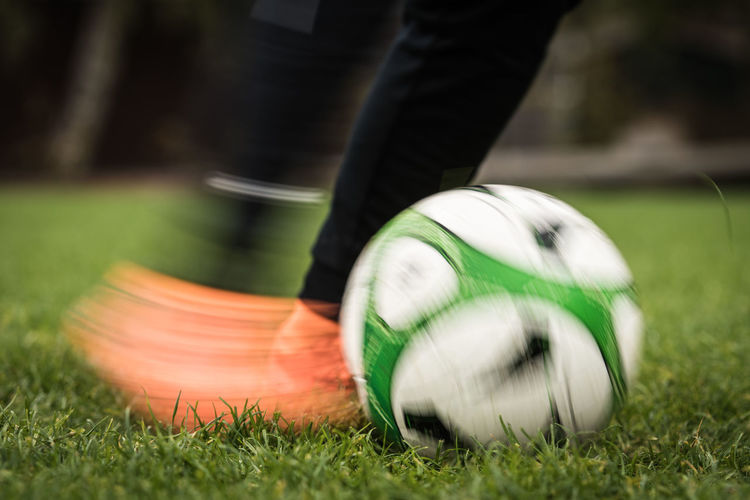 Low Section Of Person Kicking Soccer Ball On Field