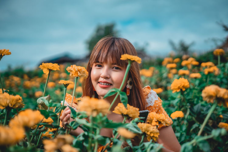 Portrait of girl with yellow flowers on field